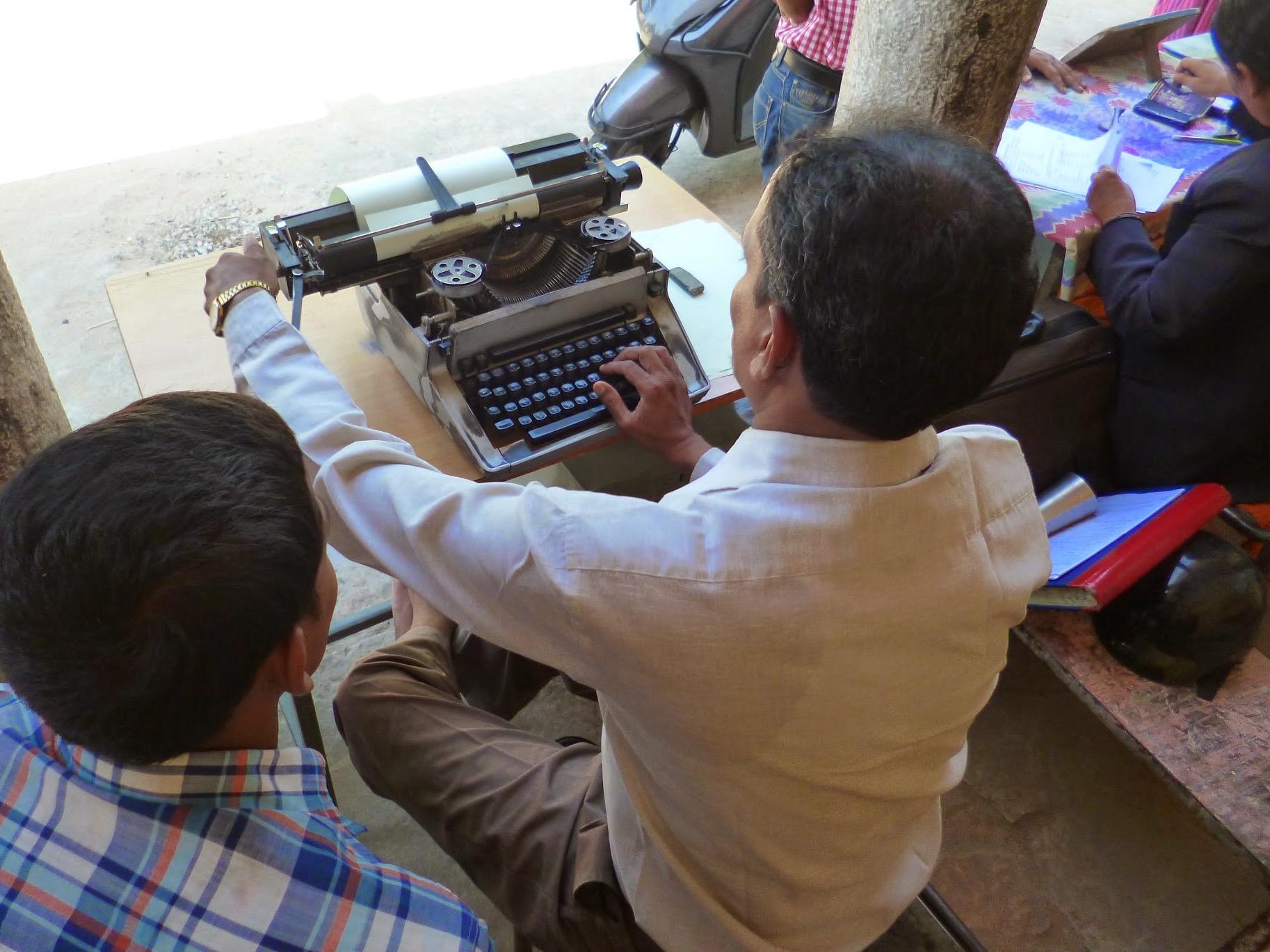 Man working on typewriter, image by Media Helping Media